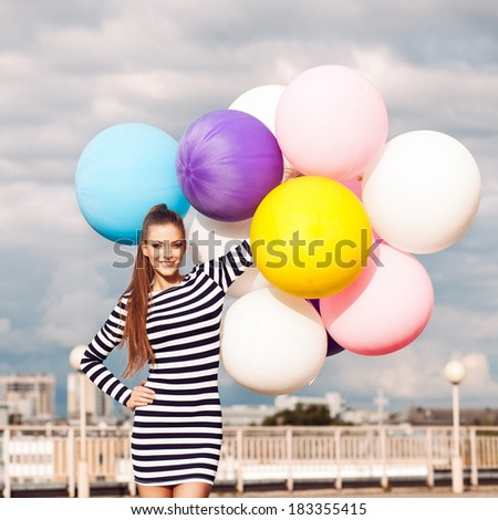 beautiful young lady in black and white striped short dress holds a bunch of multicolored balloons smiling for camera - stock photo