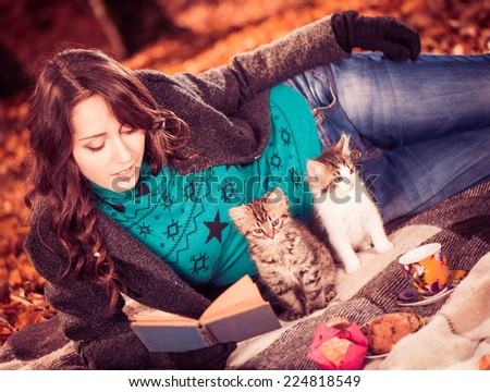 beautiful young lady in coat with two cats reading book on a plaid at fall forest