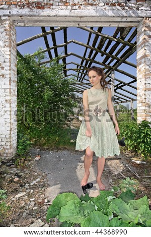 Beautiful Young lady in light-green evening dress standing barefoot under arch of deserted brickwall building