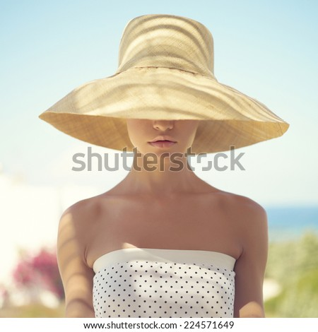 Beautiful young lady in straw hat in the sunlight - stock photo