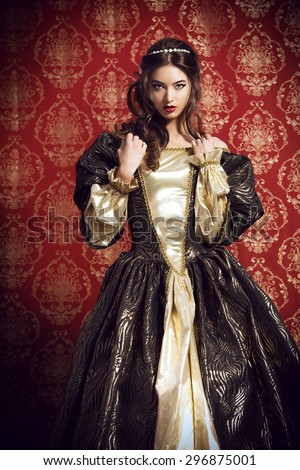 Beautiful young lady in the lush expensive dress posing over vintage background. Renaissance. Barocco. Fashion. - stock photo