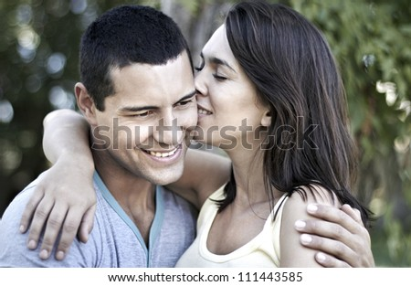 Beautiful young lady kissing attractive young man on his cheek - stock photo