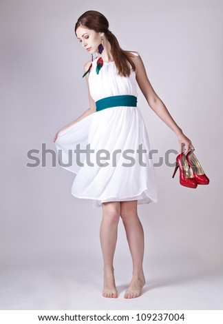 Beautiful young lady posing in white dress with bright accessories