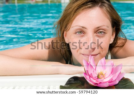Beautiful young lady relaxing at the edge of a swimming pool with lotus flower - stock photo