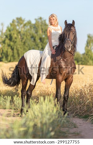 Beautiful young lady riding black stallion. - stock photo