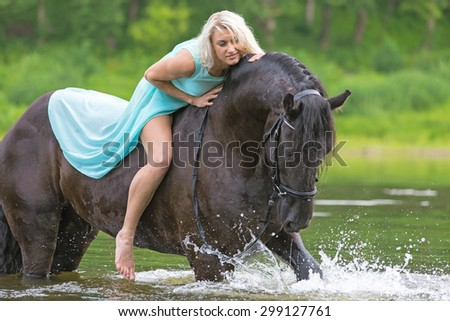 Beautiful young lady riding black stallion. - stock photo