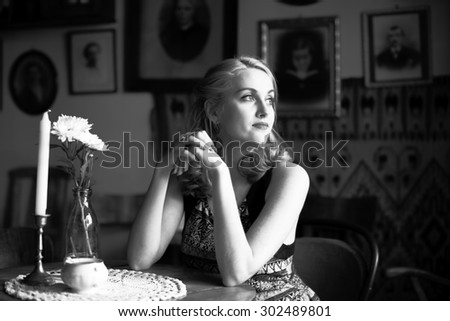 Beautiful young lady sitting at a table, a black-and-white portrait in retro style.