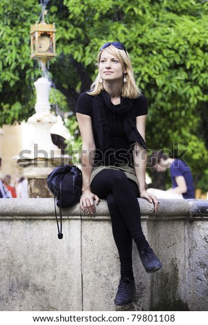 Beautiful young lady sitting at the edge of the fountain at the main square in Cordoba, Spain, on a sunny day. - stock photo