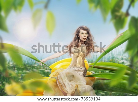 Beautiful young lady sitting on a tulip - stock photo