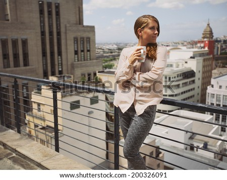 Beautiful young lady standing by a railing on terrace holding a cup of coffee looking away. Caucasian female drinking coffee and enjoying city view from balcony. - stock photo