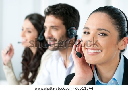 Beautiful young lady talking on headset at call center office - stock photo