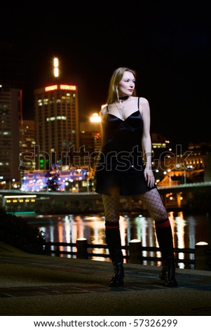 Beautiful young lady waits by the riverside at night