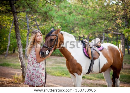 Beautiful young lady wearing vintage dress riding a horse at sunny summer day. Blond long hair with and a happy smile. Perfect skin and makeup. Close up. Outdoor shot.