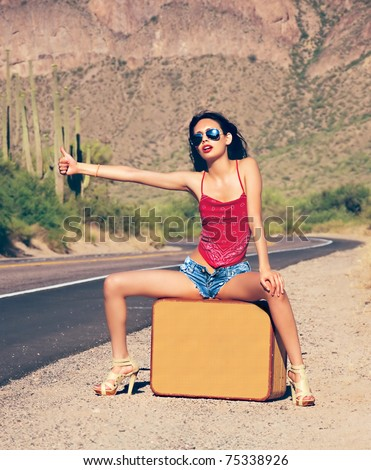 Beautiful young lady with case hitching a ride on a lonely hot desert road - stock photo