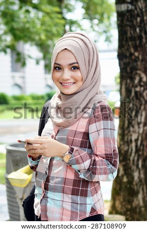 Beautiful young lady with smart phone computer in the garden - stock photo