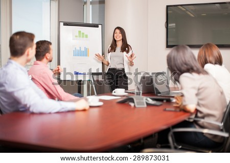 Beautiful young Latin brunette giving a business presentation to some of her clients in a meeting room - stock photo