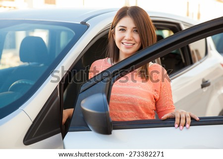 Beautiful young Latin brunette standing next to her car and smiling - stock photo