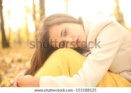 beautiful young latin hispanic brunette woman in yellow autumn park Copy space for inscription sits wrapped in a blanket with a dreamy and sad face looking down and not at the camera - stock photo