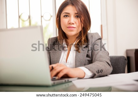 Beautiful young Latin lawyer doing some work on a laptop computer - stock photo
