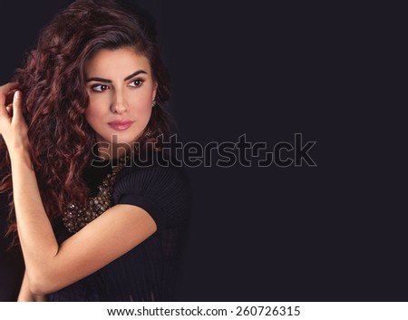 Beautiful young latin woman face, holding her long wavy hair, looking to the left and thinking on a black background with empty copy space - stock photo