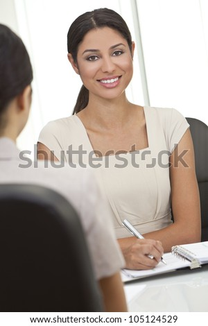 Beautiful young Latina Hispanic woman or businesswoman sitting at a desk in an office having a meeting