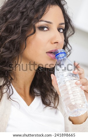 Beautiful young Latina Hispanic woman smiling, relaxing and drinking a bottle of water - stock photo