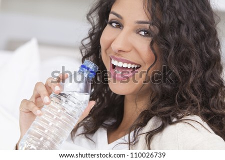 Beautiful young Latina Hispanic woman smiling, relaxing and drinking a bottle of water at home on a sofa - stock photo