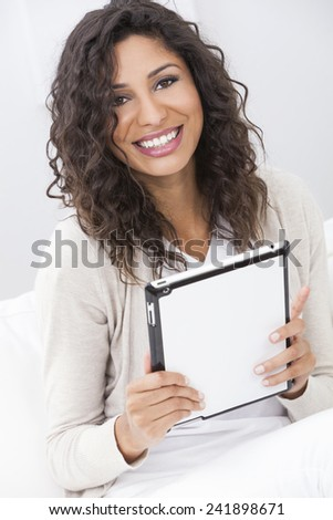 Beautiful young Latina Hispanic woman smiling, relaxing and using a tablet computer - stock photo