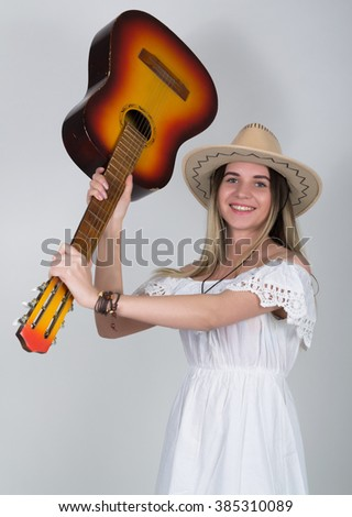 beautiful young leggy blond Country girl in a litl white dress and cowboy hat with a guitar - stock photo