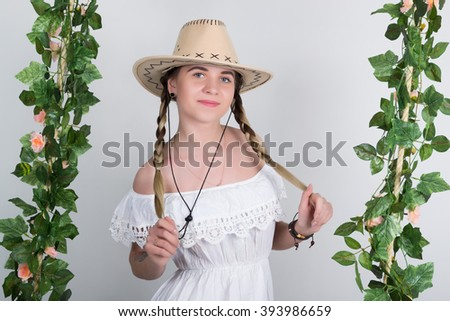 Beautiful young leggy blonde in a little white dress and white cowboy hat on a swing, wooden swing suspended from a rope hemp, rope wrapped vine and ivy. she keeps herself pigtails. - stock photo