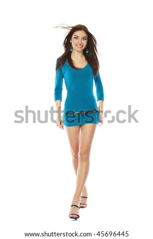 Beautiful young leggy brunette in a little blue cocktail dress full height - stock photo
