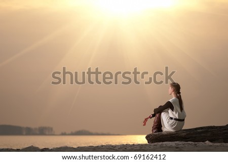 Beautiful young lonely woman sitting on sea coast at autumn sunset - stock photo