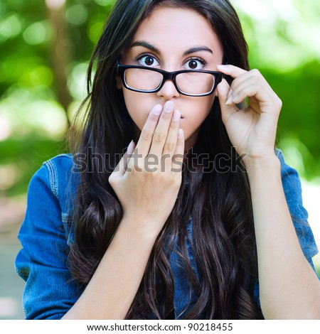 beautiful young long-haired woman glasses surprised covers mouth - stock photo
