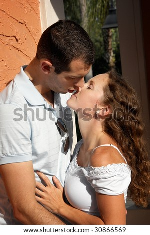 beautiful young lovers holding each other about to kiss outdoors in the hot afternoon sun in tropical setting - stock photo