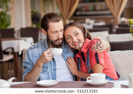 Beautiful young loving couple is drinking tea in cafe. They are sitting at the table and embracing. The girl is looking aside dreamingly and smiling. Her boyfriend is looking at her with love - stock photo