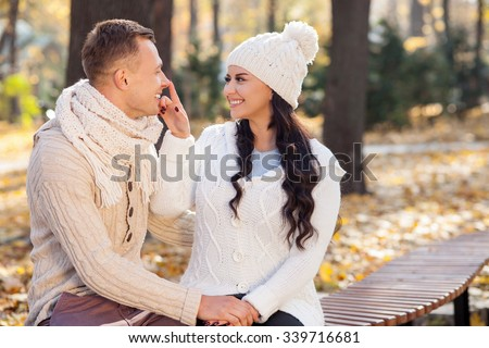 Beautiful young loving couple is sitting on bench in the autumn park. They are holding hands and smiling. The woman is touching male nose playfully. They are looking at each other with love - stock photo