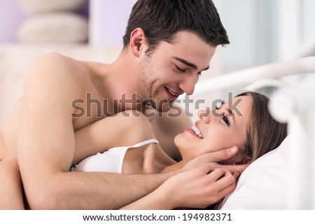 Beautiful young loving couple lying in bed - stock photo