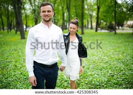 Beautiful young loving couple with tattoos walking holding hands in nature - stock photo
