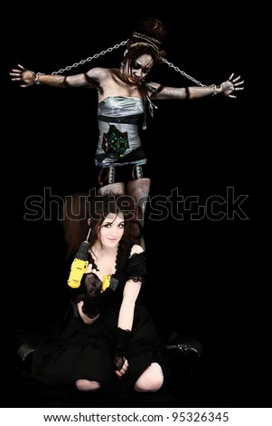 Beautiful Young Mad Scientist in gothic lolita dress with electric drill and her Cyborg Robot Prisoner Over Black. - stock photo