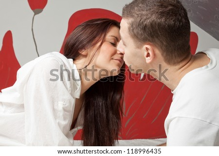 Beautiful young man and woman kissing in the bed - stock photo