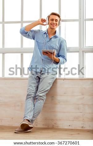 Beautiful young man in a blue shirt and light jeans, use a tablet with headphones around his neck, sitting on the windowsill at home - stock photo