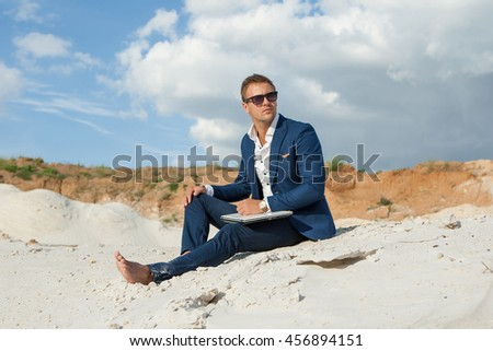 Beautiful young man in formalwear working on laptop while sitting barefoot on sand in desert enjoying nature and the sun. Peaceful place to work and leisure. - stock photo