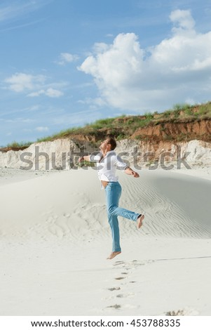Beautiful young man jumping barefoot on sand in desert enjoying nature and the sun. Fun, joy and freedom