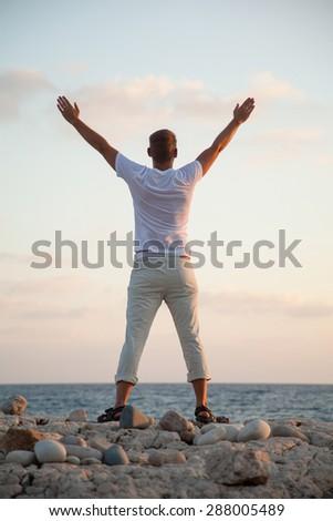 Beautiful young man on the seashore at daybreak - stock photo