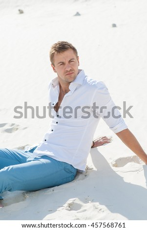 Beautiful young man  sitting barefoot on sand in desert enjoying nature and the sun. Peaceful place to leisure.