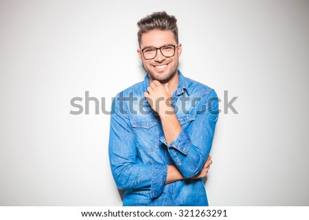 beautiful young man wearing glasses, smiling and touching his chin  - stock photo
