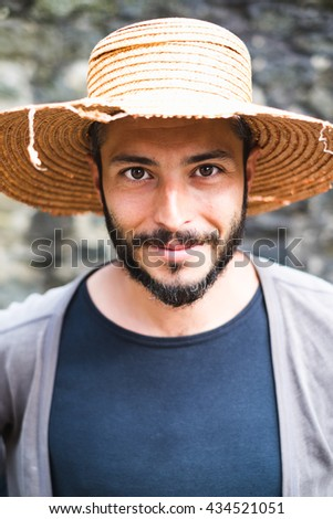 Beautiful young man with a straw hat
