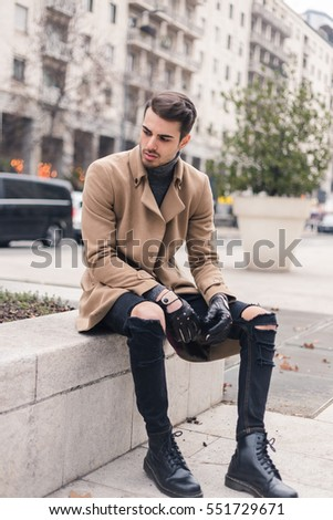 Beautiful young man with short hair posing in an urban context