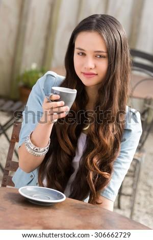Beautiful young maori woman drinking coffee - stock photo