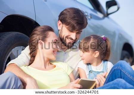 Beautiful young married couple with small daughter are sitting near car. They are making trip with joy. The father is embracing his wife and girl. They are reading book and smiling - stock photo